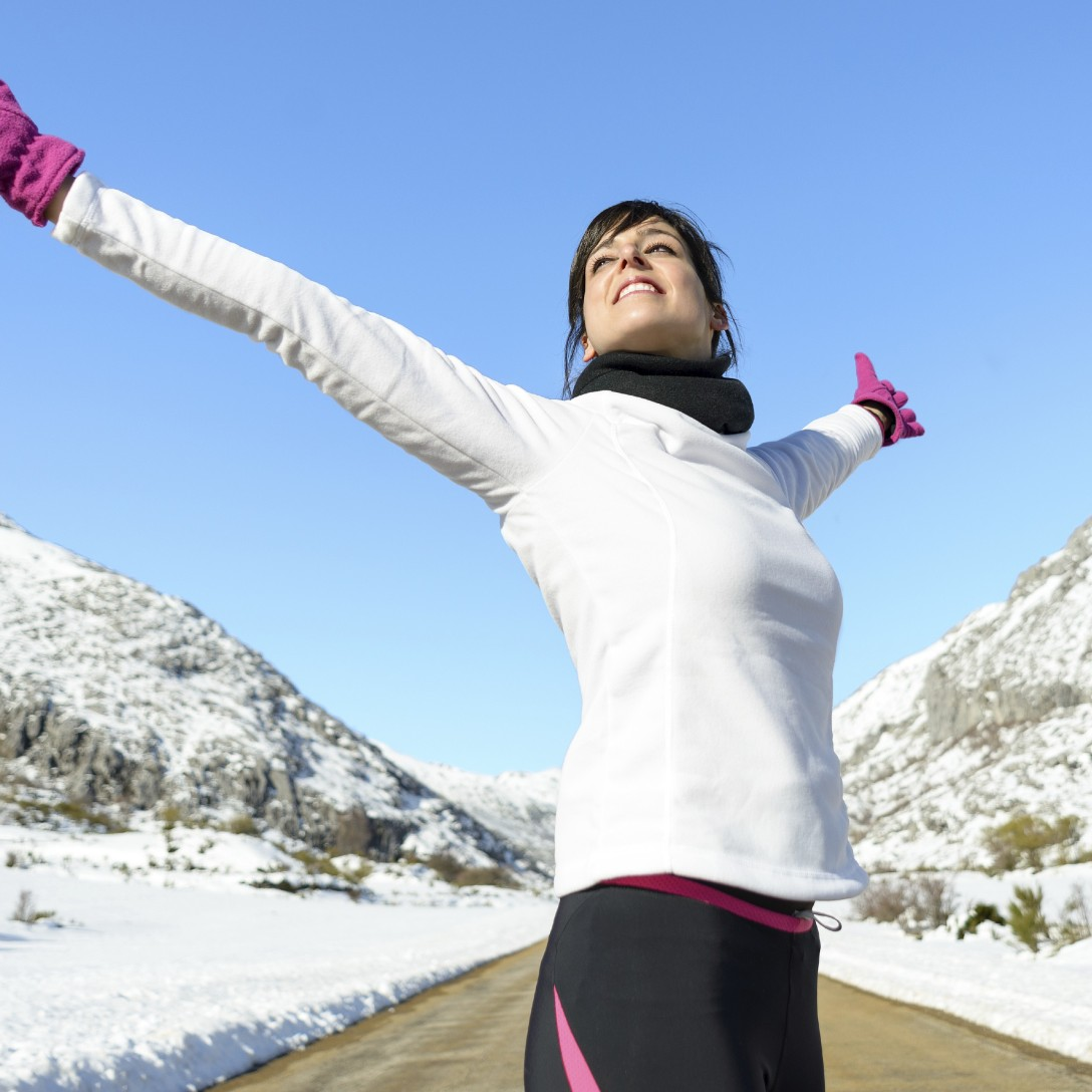 Running woman success bliss sport concept on winter road mountain background. Beautiful cheerful caucasian Female athlete with arms up.